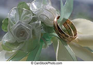 Wedding rings on a white background with satiny tapes