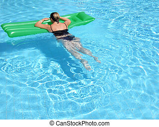 In the Pool - A woman on vacation relaxes in the pool on a...