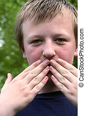 Speak No Evil - Preteen boy with mouth covered by both hands...