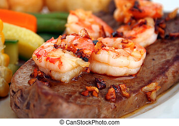 Surf n Turf - Close up of a steak with garlic butter sauce...