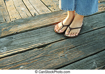 On a boardwalk - A woman\\\'s feet on a boardwalk