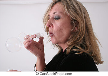 Woman blowing bubble - A blond woman is blowing bubbles in...