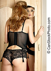 mirror - lovely lady in black lingerie looking into mirror