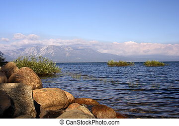 Rocky shoreline of Lake Tahoe with mountains in the...