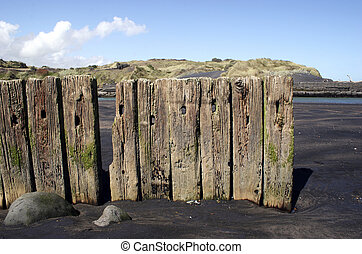 Wooden posts in black sand at Patea, Taranaki, New Zealand