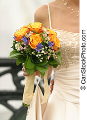 Wedding bouquet from yellow roses in hand of the bride