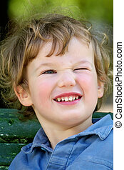 Cheerful blinking child - Boy with pleasure looks at the...