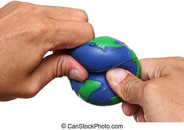 Hands Squeezing Earth - Hands squeezing Earth over a white...
