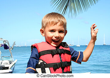 boy ready for watersports, with a safety jacket on