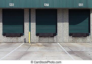 Loading bays - Three green warehouse loading bays at...