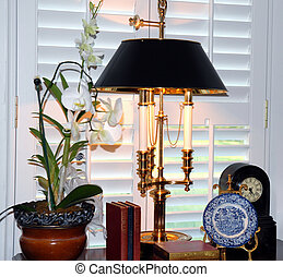 Tablescape - A tablescape with a lamp, plate, books, flowers...