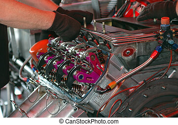 More Power - Engineer adjusting powerful race car engine.