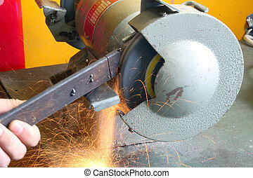 Grinder - Worker moving a bar of steel against a spinning...