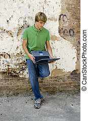 Teen with Laptop - Fifteen year old boy standing outside...