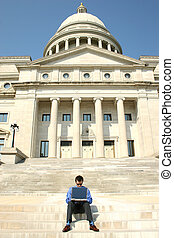 Man and Computer on Steps - Young adult male working on a...