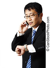Busy businessman - Businessman talking on a phone while...