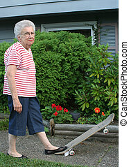 SkateboardGrandmothr - Senior citizen woman standing on...