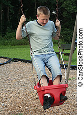 Too Big To Swing - Teenage boy standing on a baby swing.