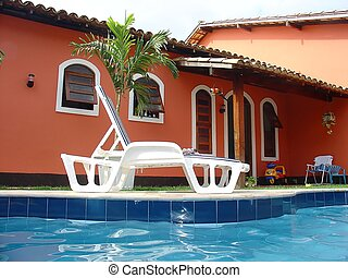 Red house with swimming pool in the backyard