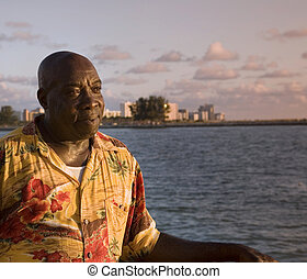 Caribbean Man Enjoys Sunset - A caribbean man enjoying a...