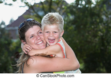 Family happiness - Cute blond boy embracing his mother with...