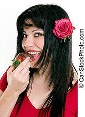 Female eating fresh strawberries in chocolate