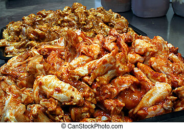Chicken wings being prepared with satay sauce