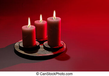 Three Candles over red background