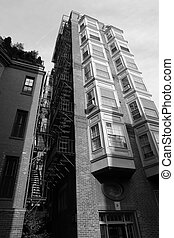 Tall building with fire escape and bay windows - black and...