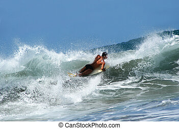 Surfer on Wave - Bodyboarder on big wave from low angle