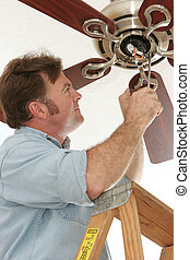 Electrician Installing Ceiling Fan - An electrician...