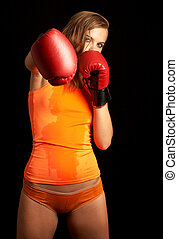 punch - sporty girl in boxing gloves punching