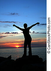 Happiness - Silhoette of girl against beauiful sunset.