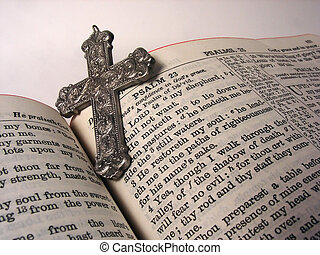 Bible and Cross - an opened bible with a silver cross