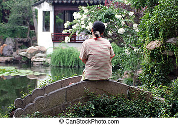 Asian garden - Woman seating on a little bridge in an asian...