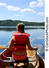 Child in canoe paddling on a scenic lake