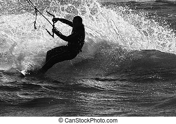 Kite Surfing - A silhouette of a kite surfer riding the wave...