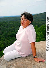 Woman edge cliff - Mature woman sitting on scenic cliff edge