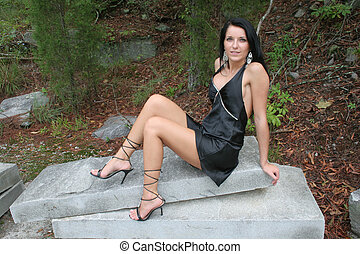 woman on rock - black haired woman in a small black dress is...