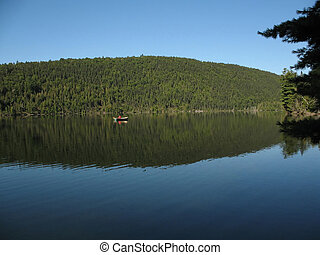 Solitary row boat on mirror-like lake - A solitary row boat...