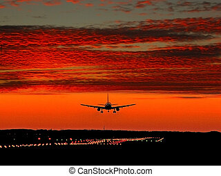 Jet landing to Munich airport in evening red