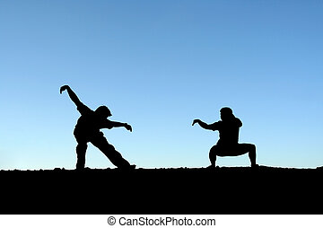 Martial arts - Two persons practicing martial arts on top of...