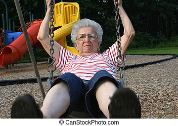SwinginGrandmother11 - Senior citizen woman on a playground...