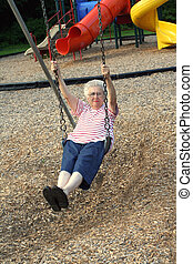 SwingingGrandmother6 - Senior citizen woman swinging on a...