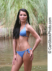 Woman in bikinni - A black haired woman is outside standing...