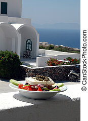 greek salad with cycladic architecture in background over...