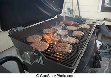 BBQ 1 - Hamburgers and hot dogs cooking on barbeque grill...