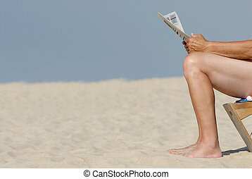 News - Older man with newspaper at the beach