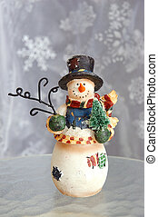 Snowman figurine on a glass surface with snowflake...