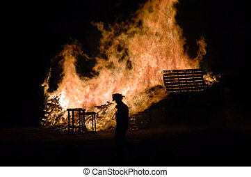 Fire - A fireman looks over large bonfires